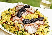 Monkfish with bacon and prunes on saffron rice