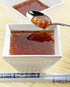 Spicy chilli sauce in bowl and on spoon