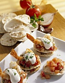 Mini-tortillas topped with tomatoes, prawns & soft cheese
