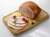 Cooked ham, partly sliced, on chopping board