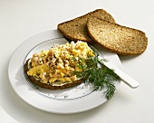 Bread topped with scrambled egg and shrimps