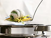 Sole rolls with vegetables on slotted spoon above pan