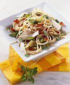 Spaghetti salad with vegetables, rocket and pine nuts