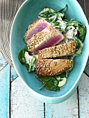 Tuna steaks with sesame seeds on spinach