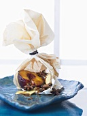 Peach with star anise & cinnamon sticks in baking parchment