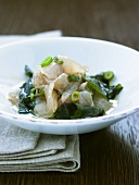 Raw fish fillets with seaweed and spring onions