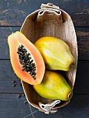 Papayas, whole and halved, in basket