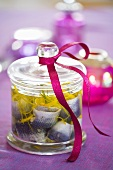 Pickled herrings with lemon zest in jar with gift ribbon