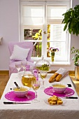 Onion soup, wine and baguettes on laid table