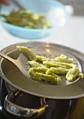 Herb gnocchi on slotted spoon over pan