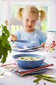 Kartoffelsuppe auf gedecktem Tisch, Kind im Hintergrund