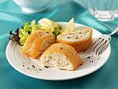 Filled salmon roulade with lemon wedges