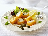 Filled salmon rolls with lemon wedges and capers