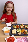 Girl with open sandwiches and vegetables