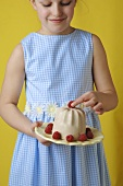 Girl holding vanilla blancmange with raspberries