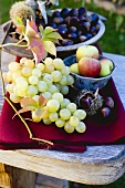 Grapes, apples, sweet chestnuts and autumn leaves