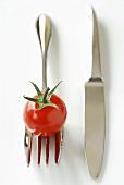 Cherry tomato on fork beside knife