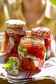 Eingelegte Tomaten in Einmachgläsern, Frau im Hintergrund