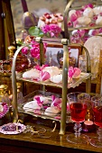 Meringues on tiered stand, liqueur and roses