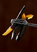 Chocolate-coated candied orange held in tongs