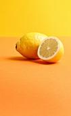 Whole lemon and half a lemon on coloured background