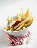 Chips with salt, ketchup, mayonnaise in white dish