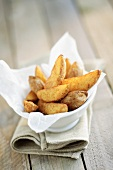 Potato wedges on paper napkin in dish