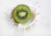 Kiwi fruit falling into milk