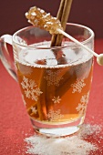 Glass of winter tea with cinnamon sticks & sugar swizzle stick
