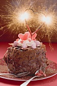 Chocolate cake decorated with sweets and sparkler