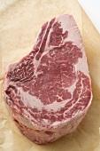 Raw beef steak on greaseproof paper