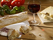Still life: bread, Parmesan, glass of red wine, basil, tomatoes