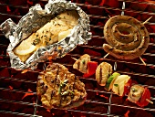 Fish in foil, meat, sausage and kebab on a barbecue
