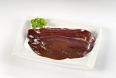 Two slices of pig's liver on rectangular plate