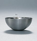 Drop of water over metal bowl