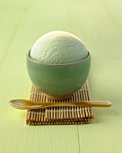 A scoop of tea ice cream in a small green bowl on bamboo mat
