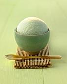 Eine Kugel Teeeis in grünem Schälchen auf Bambusmatte