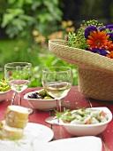 Mediterran gedeckter Tisch mit Strohhut und Blumendeko