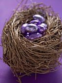 Chocolate Easter eggs in purple foil in an Easter nest
