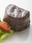 Beef fillet garnished with cherry tomato and lettuce leaf