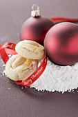 Almond biscuits and Christmas baubles on icing sugar