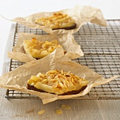 Small pear tarts with flaked almonds on baking parchment