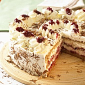 Buckwheat cake with cream and cherries, a piece removed