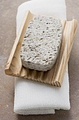 Pumice stone, wooden soap dish, towel