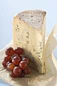 Piece of Stilton and red grapes on paper
