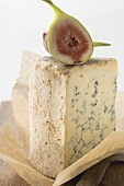 Piece of Stilton with fresh fig on paper