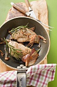 Pheasant breast with bacon and rosemary in frying pan