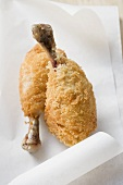 Two breaded chicken legs on paper