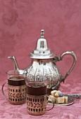Two glasses of black tea, sugar cubes, silver teapot