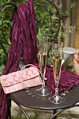 Two champagne flutes on garden chair